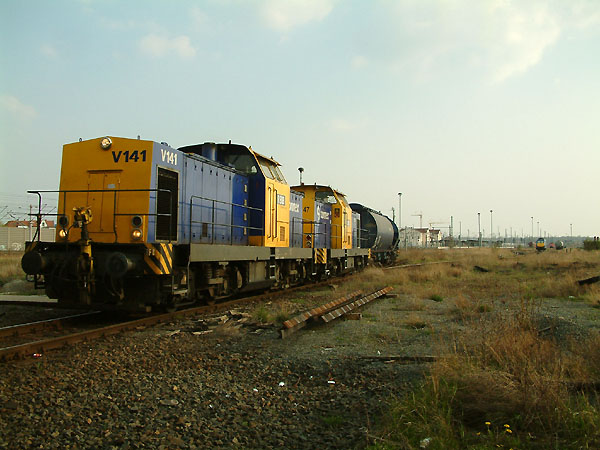 Zurück ins RBB-Depot fahren die beiden V 100 Lokomotiven V141 und V147 am Abend des 16.04.2004. Dabei nehmen sie im Bitterfelder Bahnhof noch die wenig vorhandenen Gütergleise in Beschlag.