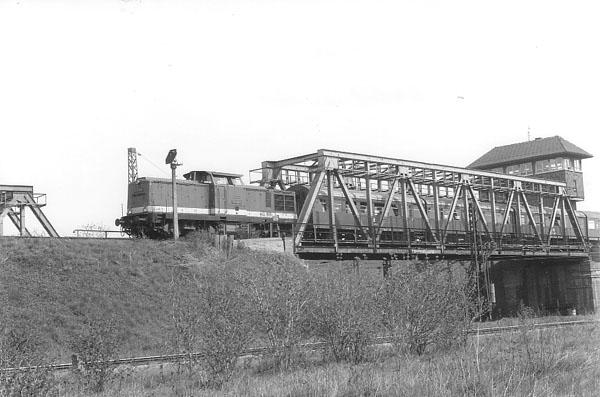 Zwischen Bitterfeld und Grube Antonie ist am 24.04.1987 der P 19574 mit der Diesellok 110 018 unterwegs. Das Stellwerk (Bild rechts) wird seit Oktober 2002 nicht mehr genutzt.