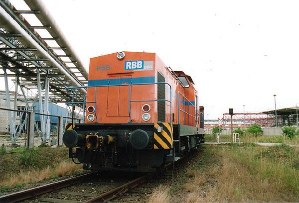 In Bitterfeld Nord rangiert am 31.03.2000 die V100-Diesellok der Regiobahn Bitterfeld (RBB) einige Schrott- und Holzwagen umher.