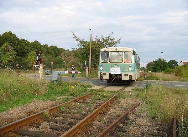 Der vollbesetzte Triebwagen verlässt den Bahnhof Zörbig und überquert einen Bahnübergang.