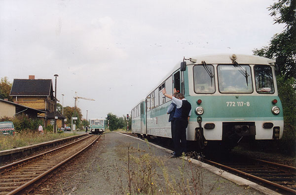 Nach der Ankunft der RB 37490 mit 771 034 (links) im Bahnhof Sandersdorf, macht sich auch am 26.09.2001 das Gespann 772 117 mit dem Steuerwagen 972 717 (RB 37490) startklar nach Stumsdorf. Das Zugpersonal gibt zuvor der ortsansässigen Fahrdienstleiterin, die Quittung für den erhaltenen Abfahrauftrag, durch entsprechende