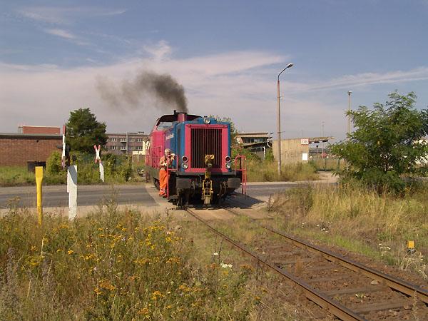 Die V 133 kreuzt am 12. August 2004 in Bitterfeld den Bahnübergang der Parsevalstraße und nimmt gerade volle Fahrt auf.
