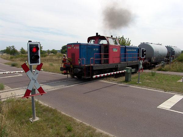 Die Infrastruktur des Bahnunternehmens reicht bis in das benachbarte Gewerbegebiet Wolfen/Thalheim. Die V 133 zieht am 12. August 2004 zwei Quarzwagen hinter sich her, die für das Flachglaswerk von Guardian bestimmt sind.