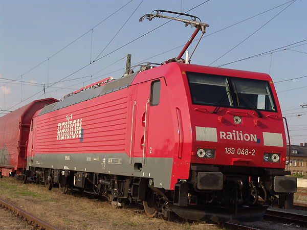 Neu aufgestellter Unternehmensbereich, neuer Schriftzug und neue Lok. Die 189 048 präsentierte sich am 10. August 2004 in Bitterfeld vor ihrem Güterzug.