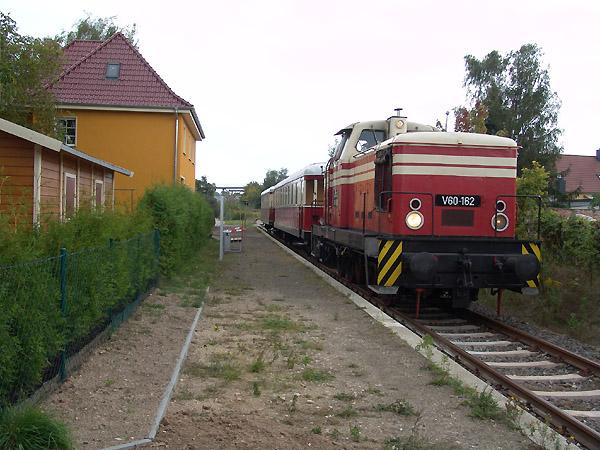 Nach dem August-Hochwasser im Jahr 2002, das auch das Bahnhofsgebäude von Dessau-Waldersee in Mitleidenschaft versetzte, ist die Sanierung des Gebäudes fast abgeschlossen und zeigt sich im gelben Outfit. Dieser wurde am 11. September 2004 mit V 60 162 und ihren beiden Reisezugwagen in Szene gesetzt.
