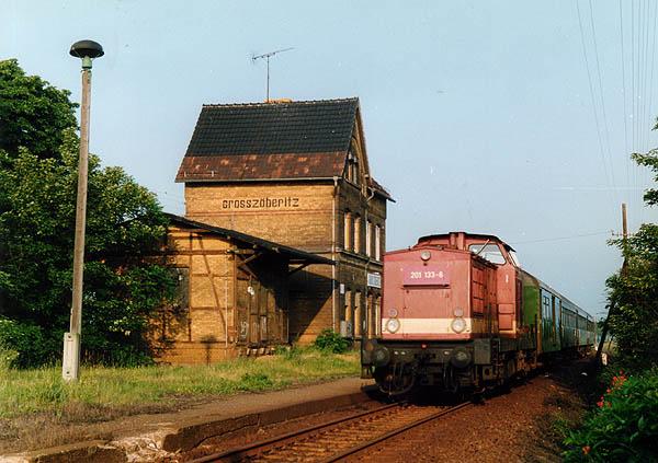 Ein langer Personenzug aus Stumsdorf ist soeben in Großzöberitz zum stehen gekommen. Hinter der Lok befindet sich noch ein dreiachsiger Postwagen / Gepäckwagen, der noch bis zum Jahr 1993 im Zugverband mitlief.