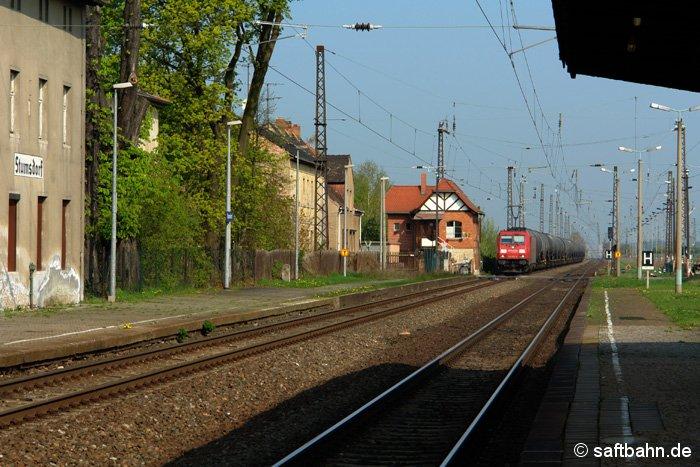 Auf dem Bahnhofsgleis 1 ist am 15.04.2009 ein Ölkesselzug mit E-Lok 185 252-4 unterwegs und passiert gerade den beschrankten Bahnübergang am Stellwerk B2.