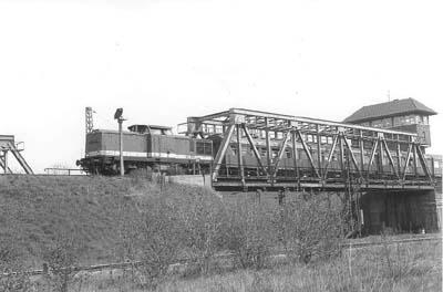 Zwischen Bitterfeld und Grube Antonie, ist am 24.04.1987 der P 19574 mit der Diesellok 110-018 an der Spitze, unterwegs. Das Stellwerk im rechtes Bildteil wird heute nicht mehr genutzt.