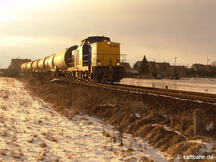 Der Abendsonne entgegen: Aus Richtung Zörbig ist der kurze Biokraftstoffzug mit Diesellok V141 unterwegs. In Heideloh befährt der Zug am 13.03.2006 das noch nicht sanierte Bahngleis in Richtung Bitterfeld, welches erst in den darauffolgenden Sommermonaten oberbautechnisch durchgearbeitet wird.