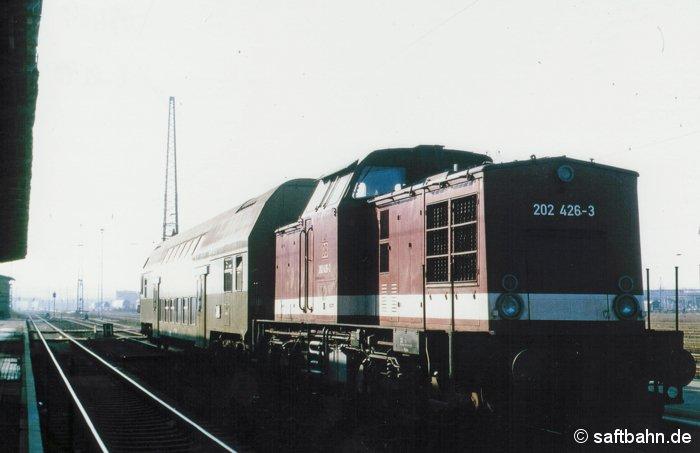 Nahverkehrsszenarie am 24.10.1995: Diesellok 202 426-3 ist soeben als Regionalbahn 8128 aus Stumsdorf mit dem Doppelstocksteuerwagen am Bitterfelder Bahnsteig 5 eingefahren und gönnt sich nun eine dreistündige Pause. Die Doppelstocksteuerwagen kamen mit dem Fahrplanwechsel im Mai 1995 auf die Strecke. Das Lokumsetzen in Stumsdorf und Bitterfeld entfiel, sodass die Umsteigemöglichkeiten zu den Anschlusszügen für die Reisenden verbessert werden konnten.