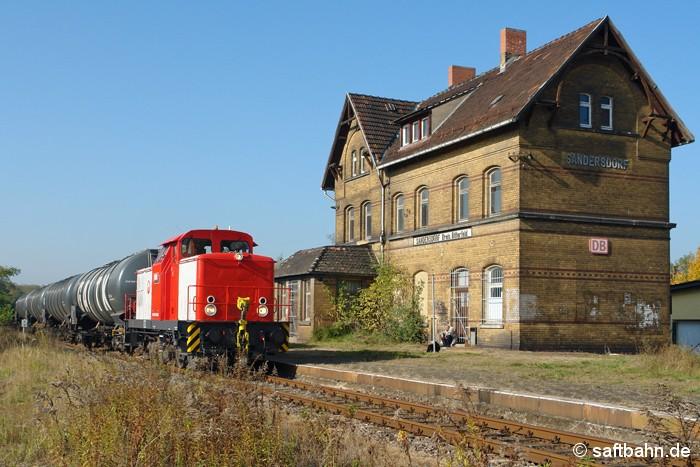 Die frisch Hauptuntersuchte V60-Lok 345 229-9 der Regiobahn Bitterfeld befindet sich am 13.10.2008 mit ihrem Ethanolkurzzug aus Zörbig gerade auf Durchfahrt in Sandersdorf, als sie vor der damals noch unbewohnten, unsanierten Gebäudessilhouette des gleichnamigen Ortes vorüber fuhr.
