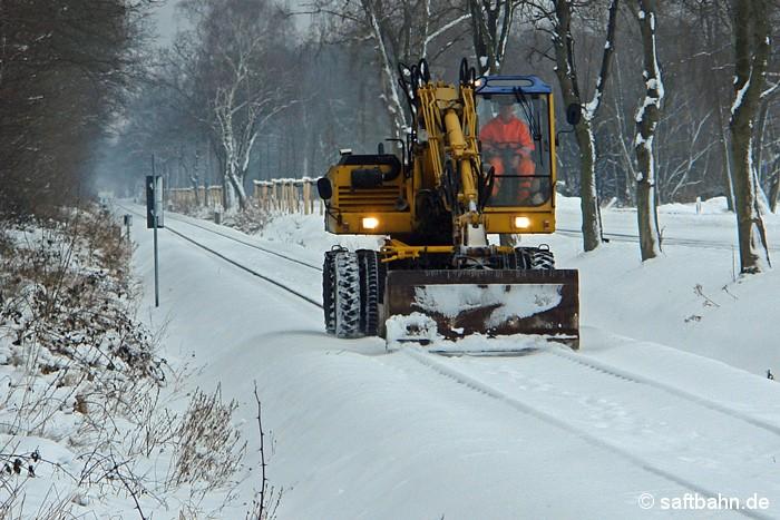 Auf Schneeschiebefahrt war am 29.12.2010 ein Zweiwege-Bagger bei Heideloh unterwegs: Heftige Schneefälle mit Schneeverwehungen machten die Saftbahnstrecke im Winter 2010/2011 zu schaffen. Immer wieder musste die Schiene geräumt werden, damit Güterzüge fahren konnten.